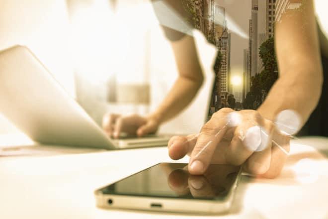 Smartphone und Computer mTAN Sicherheitslücke im Telekommunikationsnetz ermöglichte jahrelanges Umleiten von mTANS bigstock Business People Holding Mobile 154785140 660x440